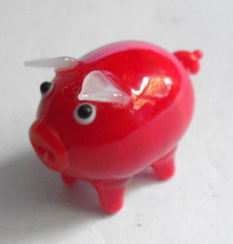 Tiny red glass piglet